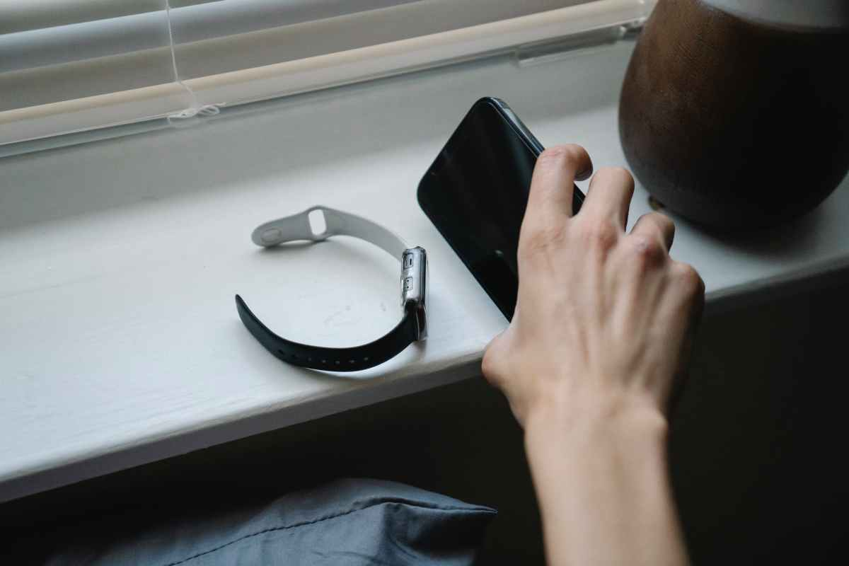 person with smartphone and wristwatch in bedroom