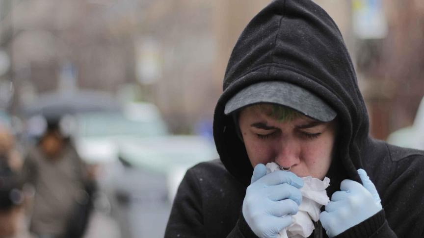 A person coughing into a tissue