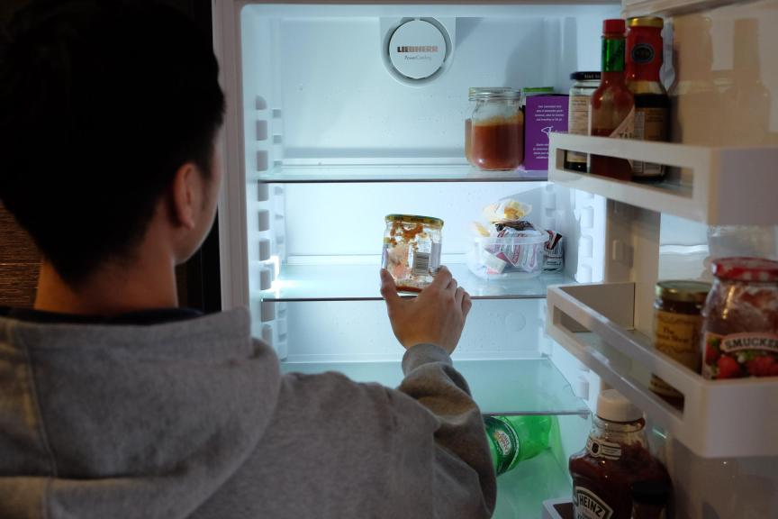 A student looks into an empty fridge