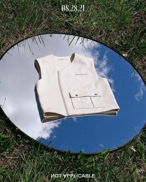 A white vest on a mirror placed on grass while its facing the sky