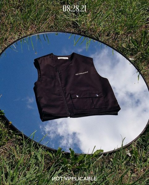 A black vest on a mirror placed on grass while its facing the sky