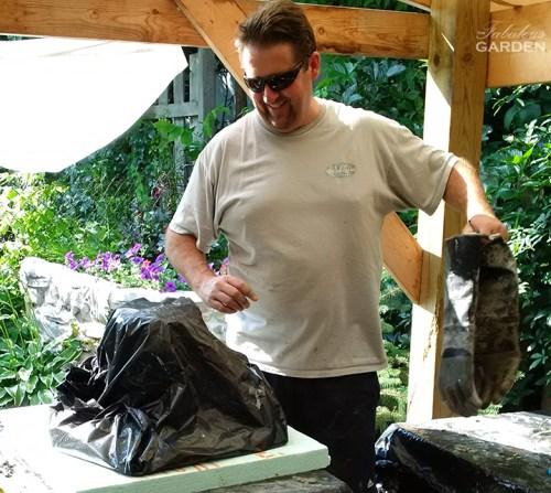 man admires black plastic garbage bag covering wet cement