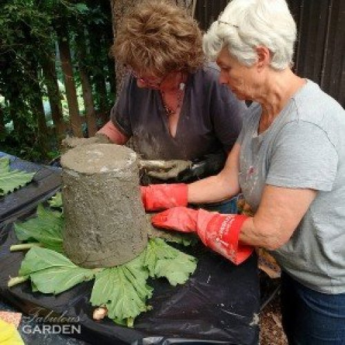 2 women put cement on planter form