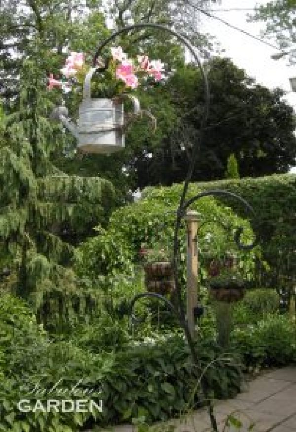 watering can with plants, hanging on a shepherd's hook