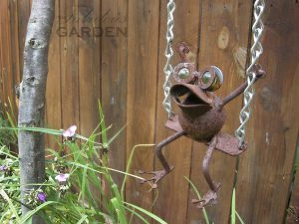 Metal frog on a swing