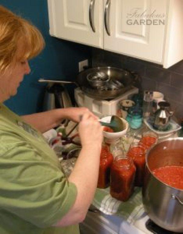 Jean ladling soup into jars
