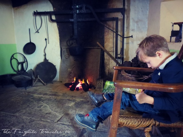 "The ""Little"" reading a map by the fire at the Bunratty Heritage Park at Bunratty castle."