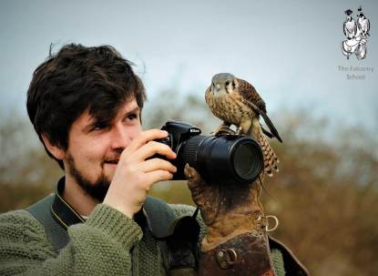 Man with bird sitting on his camera at The Falconry School