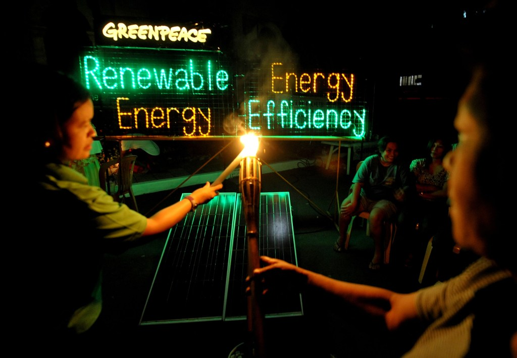 "As part of the Earth Hour program in Malate Church, volunteers from the community and the environment group Greenpeace light up candles and display an LED (light emitting diode) installation, powered by solar electricity, spelling the words ""Renewable Energy. Energy Efficiency"" to highlight the need for an 'Energy Revolution' to call for solutions to climate change. Greenpeace is using the opportunity during this year's Earth Hour to call attention to the need for commitment from political leaders to support the massive shift from dependence on climate change-causing fossil fuel to renewable energy and energy efficiency technologies."