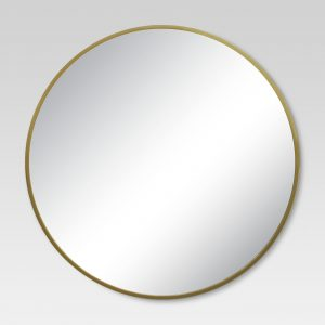 A round mirror with a gold trim.