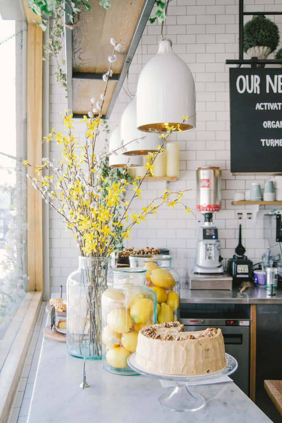 The white kitchen counter with a clear glass vase filled with yellow flowers and a cake on a stand with a piece taken out of it.