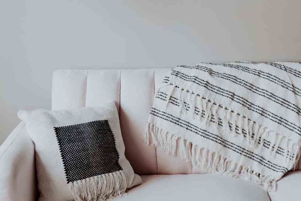 Neutral boho pillow and throw on the couch.