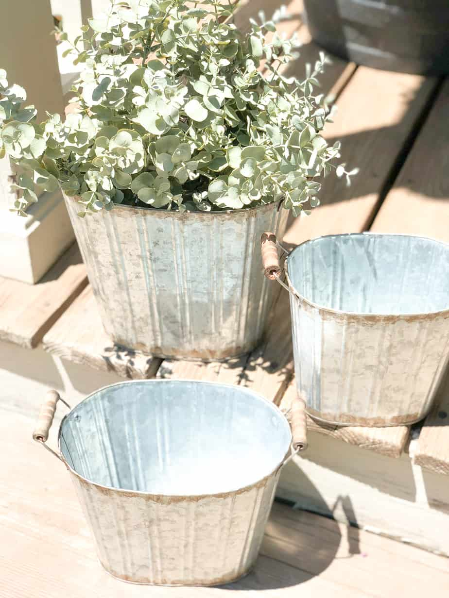 Three farmhouse buckets on the porch and stairs, with eucalyptus in one of the buckets.