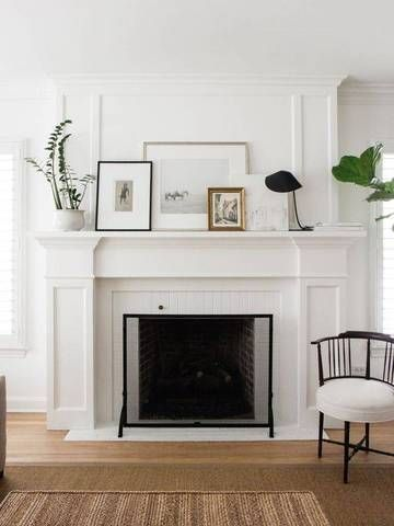A white minimalist fireplace with pictures on the mantel.