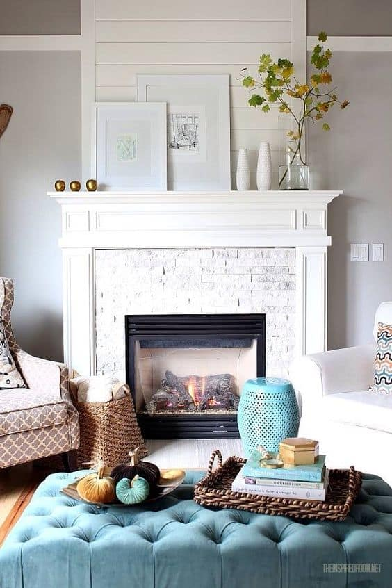 A white fireplace mantel with a baby blue ottoman in front of the fireplace.   There is a clear glass vase with a branch and green leaves on it.
