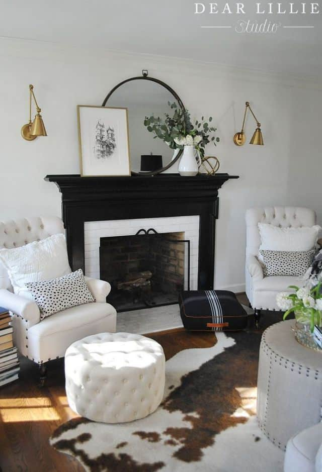 A black fireplace with gold sconces flanking it.  There are two white armchairs on either side with throw pillows on them.   A cow hide rug is in front with a white ottoman.