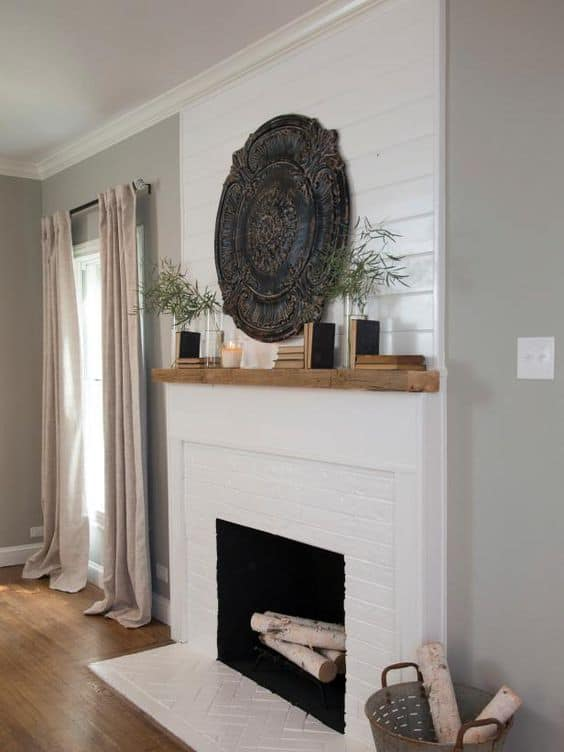 White and wood mantel with logs in the fireplace.   There are candles, vases and books on top of the mantel.