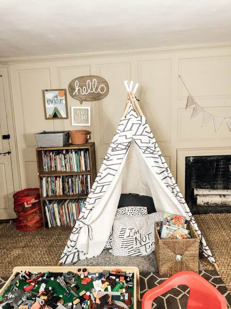 A boys bedroom with a small teepee tent in the middle of the room.  There is a bookshelf behind the tent and also a fireplace in the room.