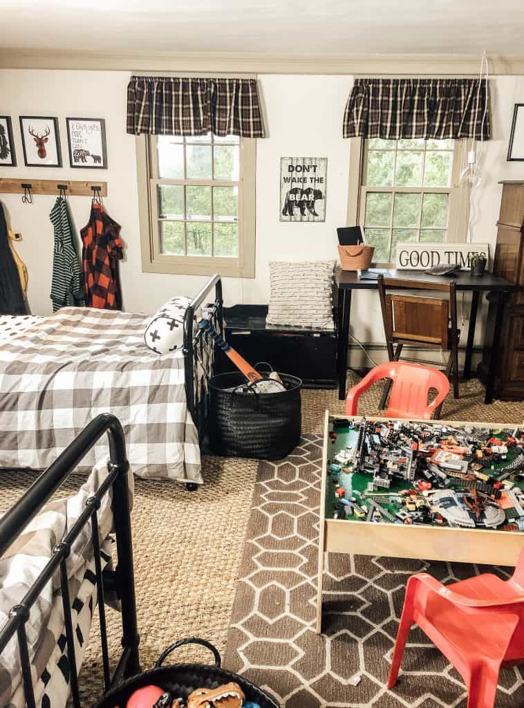 A boys bedroom with two beds in the room, toys, a small area rug and a black storage bench.