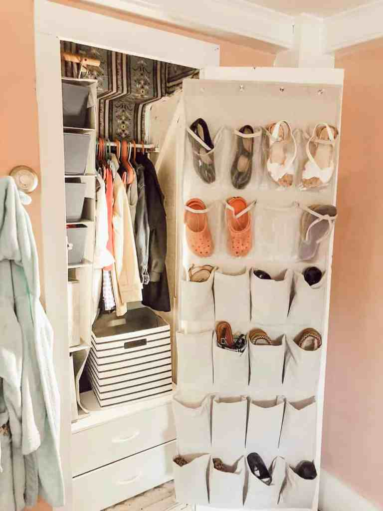 The small closet door open with shoes hanging from a rack on the door.