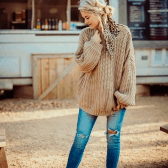 Woman in an oversized sweater, a pair of jeans and a ribbon in her hair.