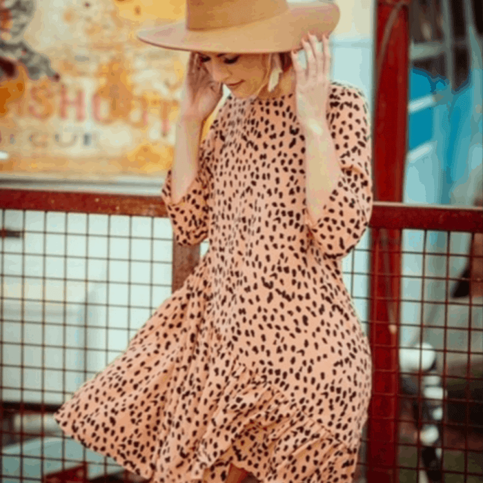 A woman in a peach sundress with a large hat on holding the hat in the wind.