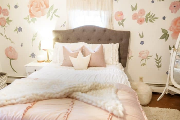 Girls pink bedroom with flowers on wall, and soft bedding in pink and white.