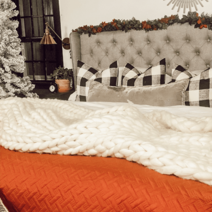 An orange and white blanket on the bed.