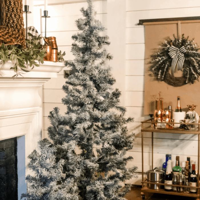 A flocked Christmas tree beside the fireplace and bar cart.
