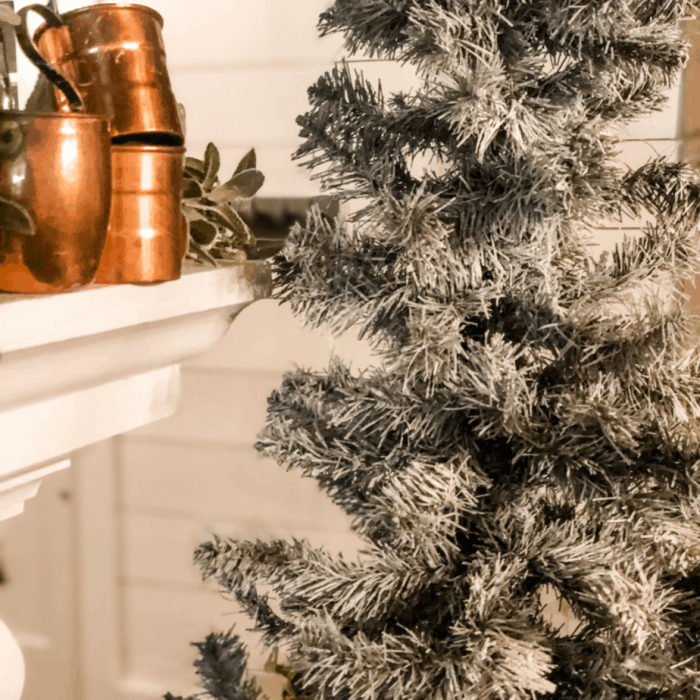 Copper pots are on the mantel beside the flocked tree.