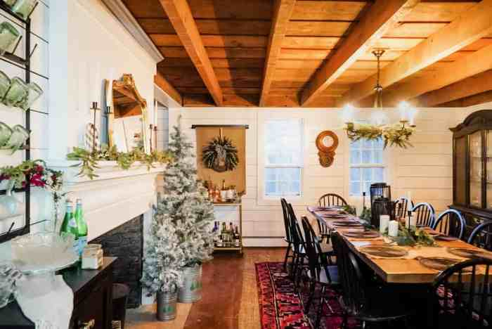 Wood ceilings long table and white flocked Christmas tree in the dining room.