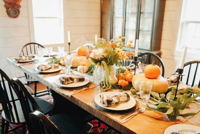 Pumpkins on table beside the floral arrangement and candles.