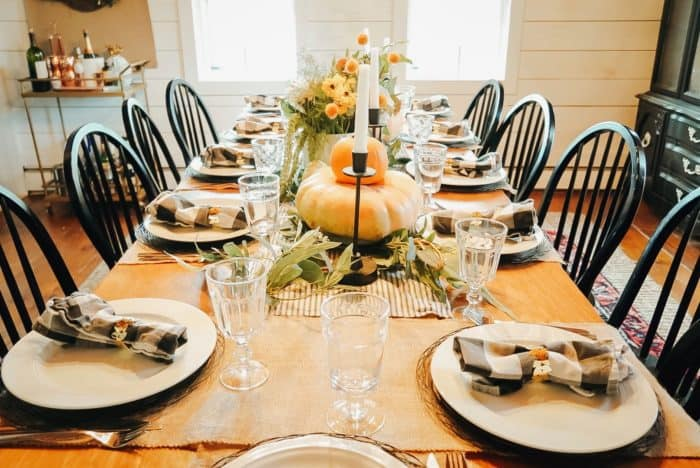 Thanksgiving table with pumpkins, burlap runner, and buffalo checked napkins.