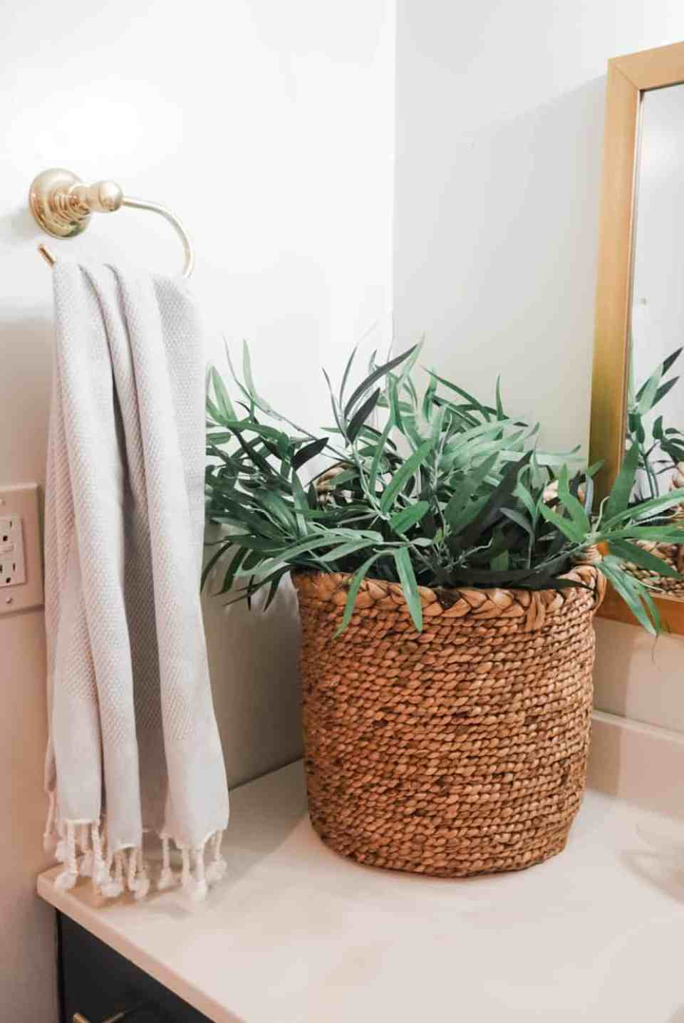 There is a basket filled with a plant on the bathroom counter.