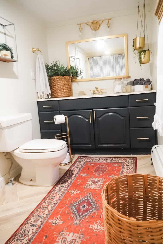 Red bathroom rug, blue vanity and gold bathroom fixtures in the bathroom.