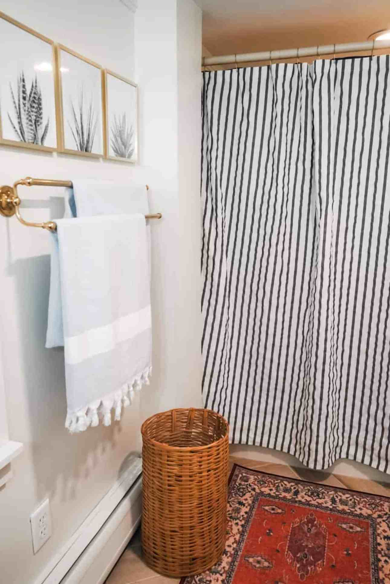 Blue and white shower curtain and towels, with three pictures on the wall and a wicker clothing hamper underneath the towel rack.