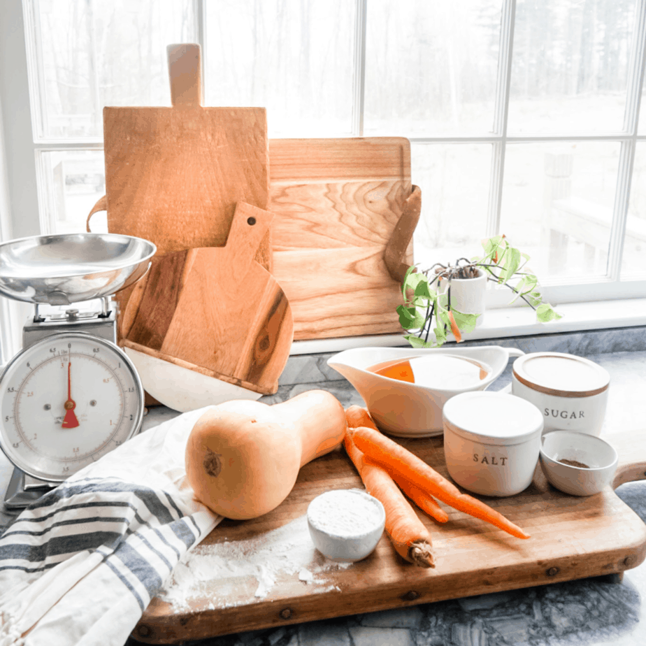 A wooden cutting board with carrots, squash, salt, and a scale all laid out for the soup.