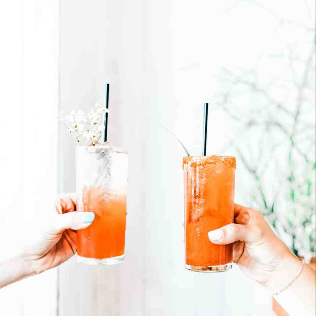 Two arms toasting two margaritas with black straws.
