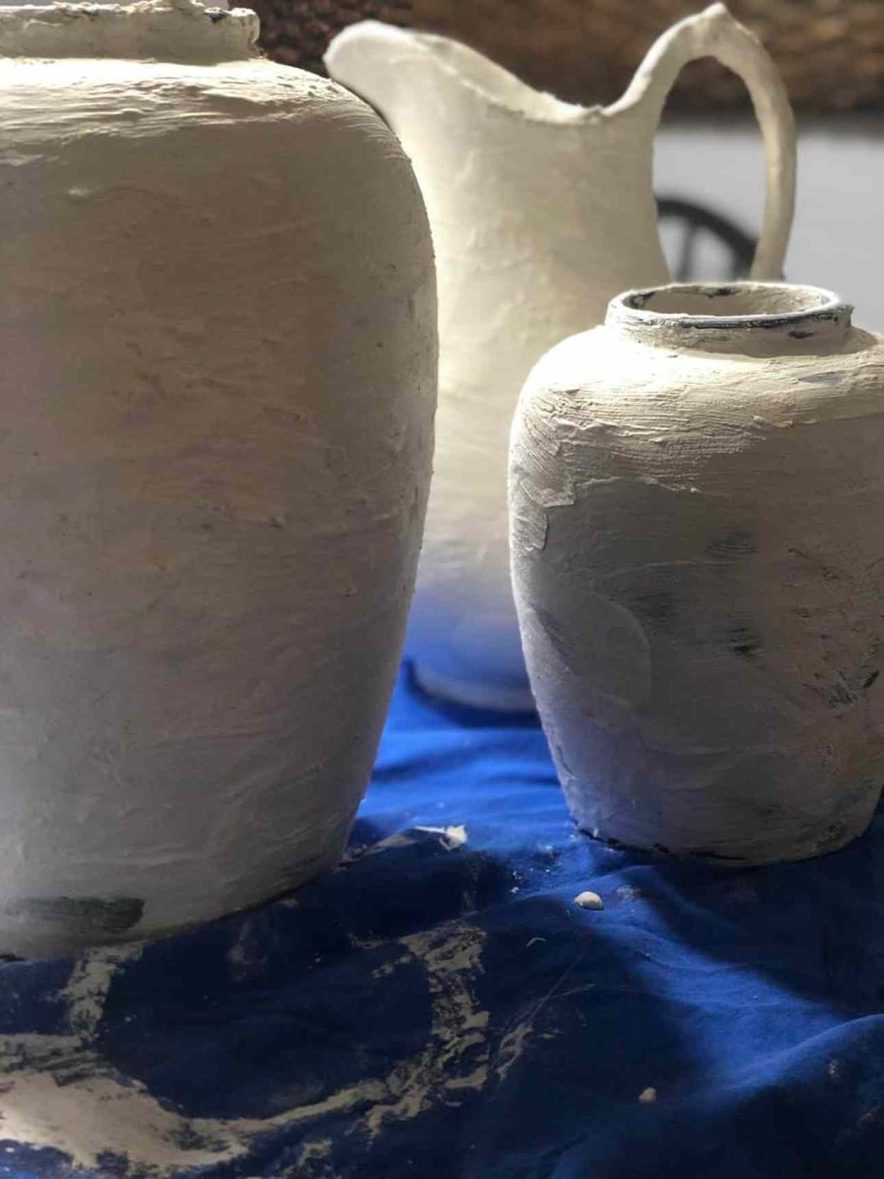 Vases covered in plaster on a blue drop sheet.