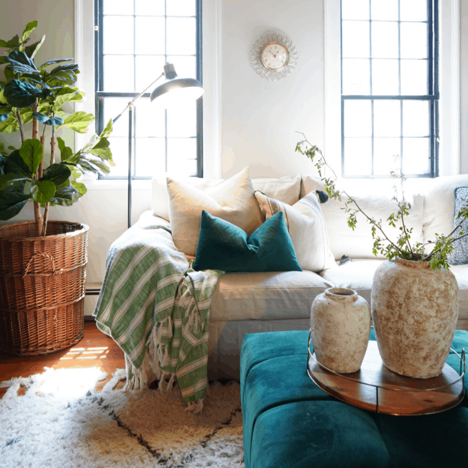 The white couch with a green and white throw blanket on it.