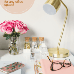 glasses on a desk with gold lamp and pink flowers