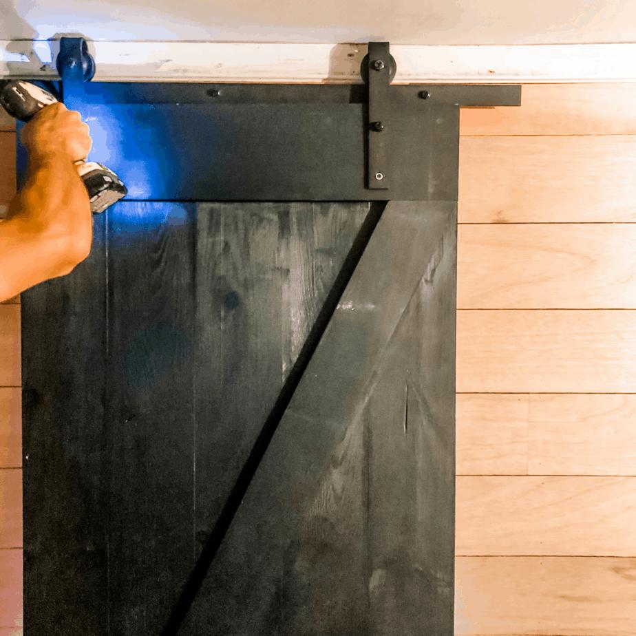Hanging barn door with screw gun.