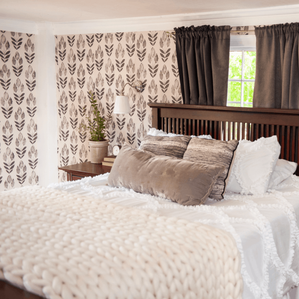 cream throw blanket on bed with wallpaper on wall