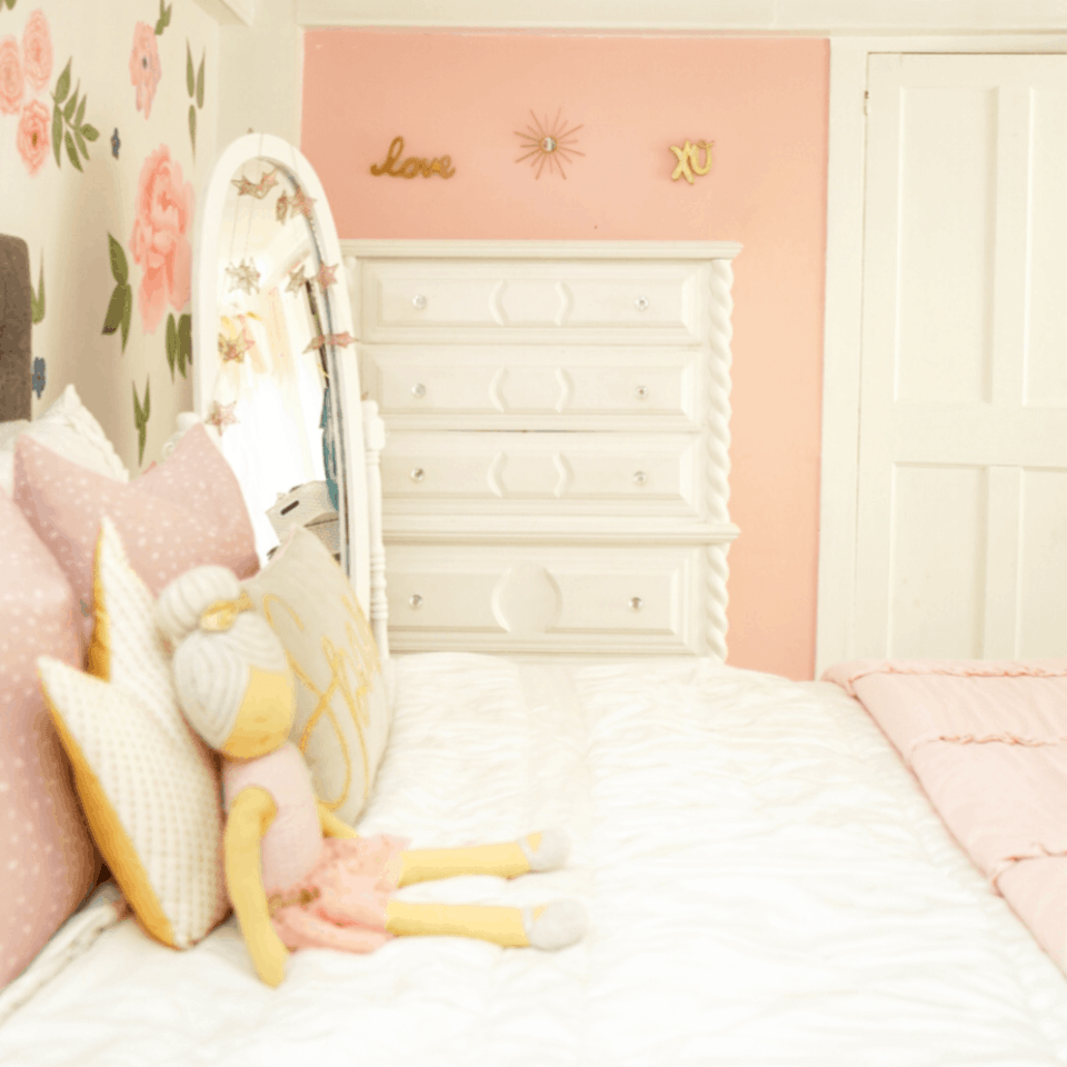 white bed with pink pillows and pink wall. white tall dresser