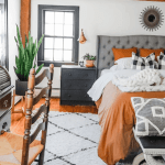 beam ceiling, gray upholstered bed, rust bedding