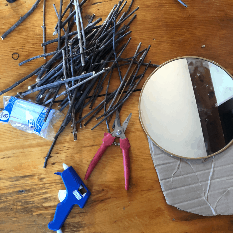 Round mirror, sticks, hot glue gun and shears laid out for the tutorial.
