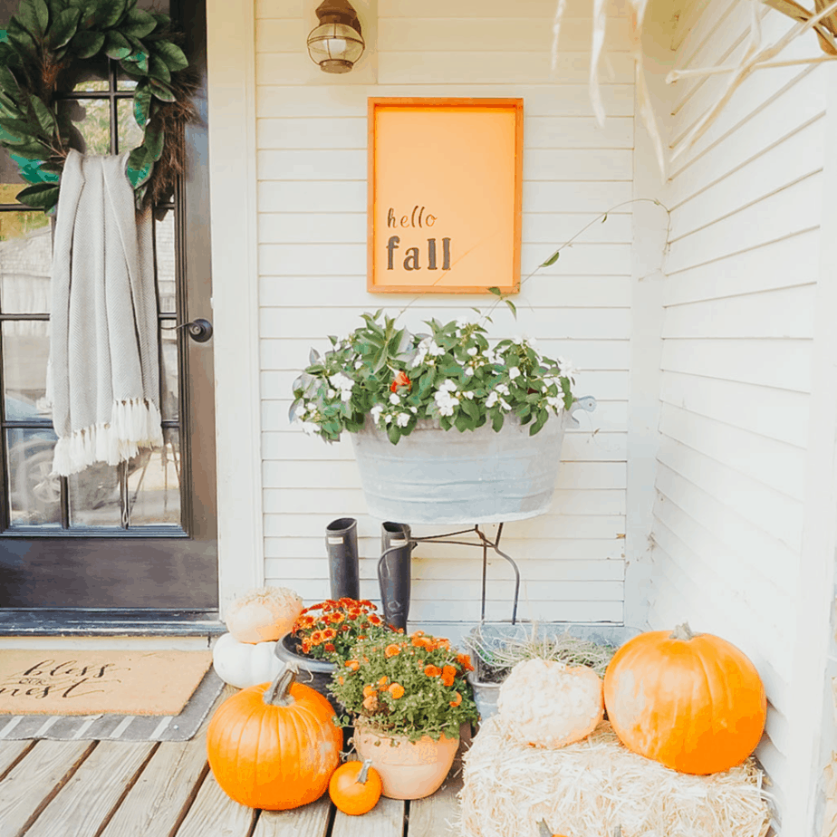 hello fall sign with mums and pumpkin on front porch