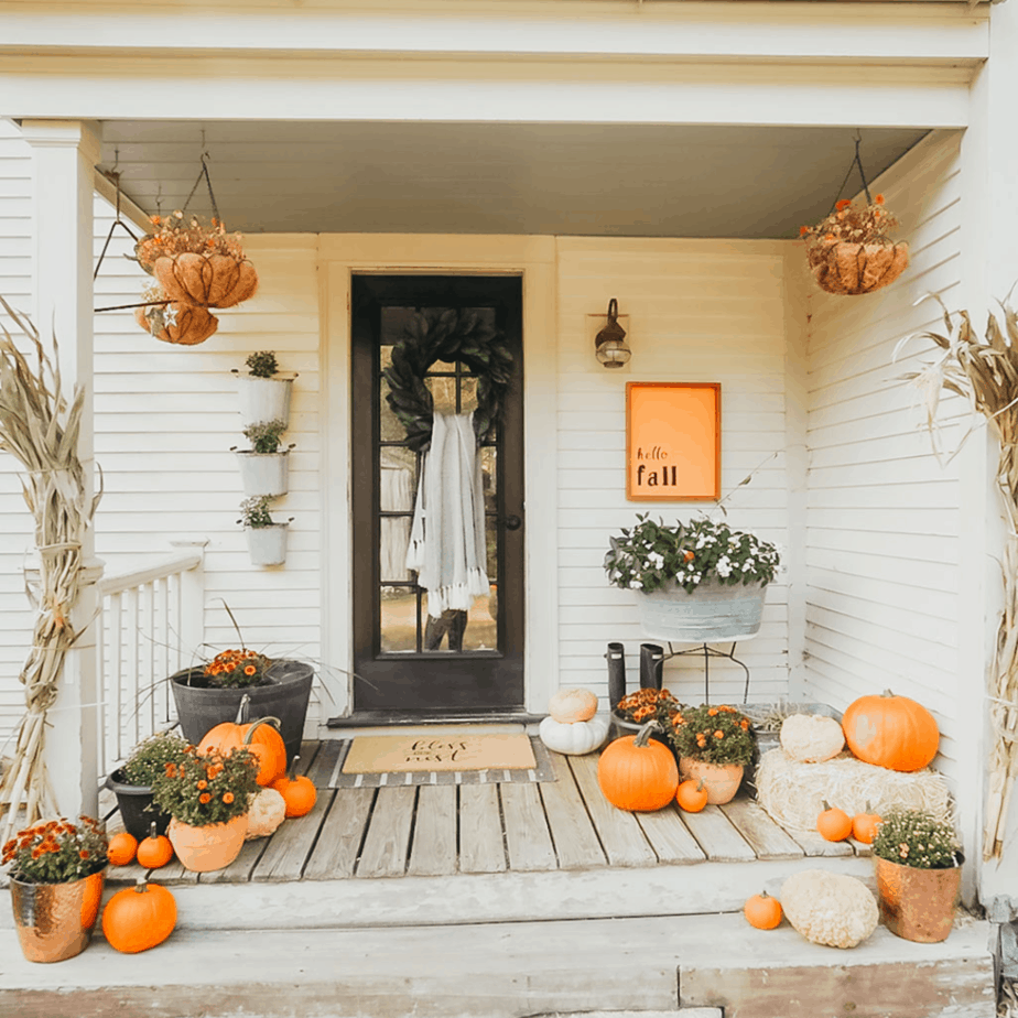 fall front porch decor with pumpkins, mums, and a green wreath