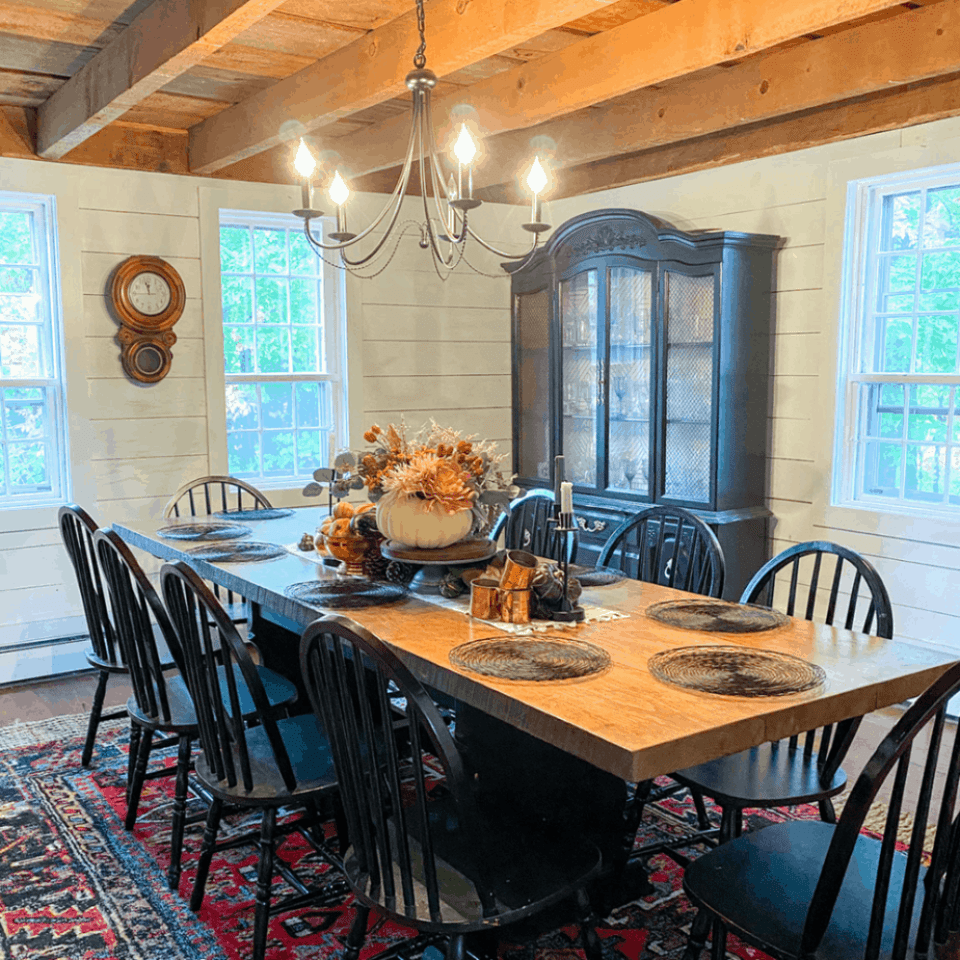 farmhouse dining room with red rug, large table, black chairs, and black light fixture