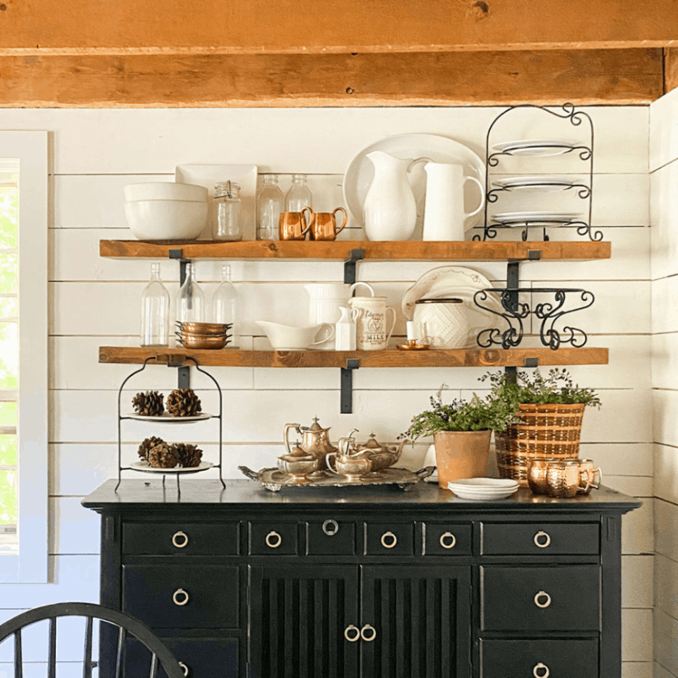 black buffet with wooden open shelves with white kitchen ware on them.